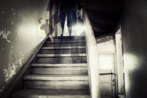 ghostly-figure-standing-on-stairs-holding-doll