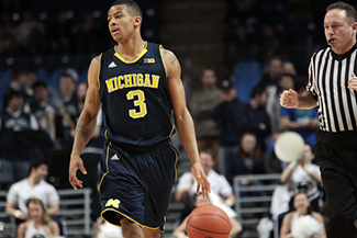 Michigan basketball player and referee on court