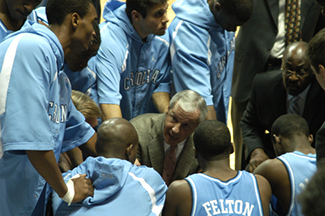 North carolina basketball players huddle around coach
