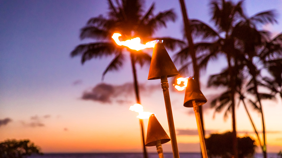 torches lit against tropical sunset
